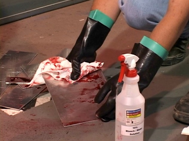 A worker using proper bloodborne pathogens safety precautions compliant with OSHA regulations