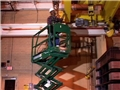 A worker on a scissor lift or aerial work platform using safe work practices to avoid injury