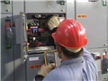 A worker demonstrating safe electrical work practices while working on an electrical panel