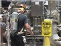 A worker wearing respiratory protection and following the Hydrogen Sulfide Contingency Plan
