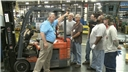 A forklift safety trainer describing safe operating procedures to a group of forklift operators