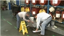 Industrial workers demonstrating good housekeeping practices after a chemical spill in the workplace