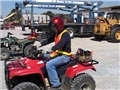 A worker demonstrating safe operating procedures while riding an all-terrain vehicle or ATV