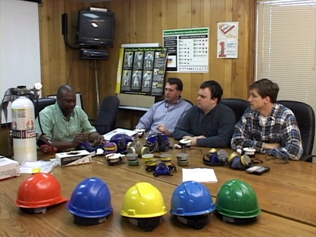 A manager training workers on the respiratory protection program and OSHA regulations standard
