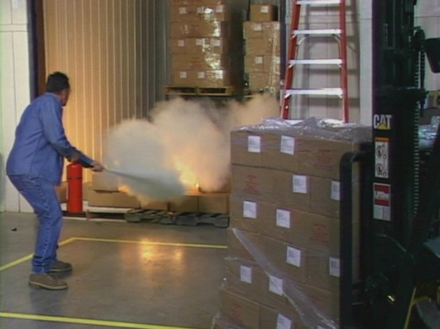 A worker that received proper training using a fire extinguisher to put out a fire in the workplace