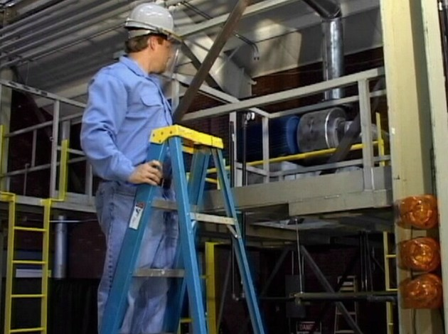 A worker using proper safety precautions and following safe work practices while using a ladder