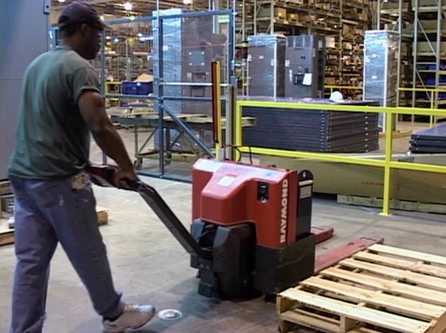 A warehouse worker safely operating an electric pallet jack to avoid injury in the workplace