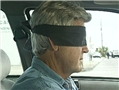 A driver wearing a blindfold to illustrate the potential hazards of the blindfold effect