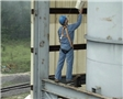 A worker using a personal fall arrest system properly to keep himself safe in case of a fall