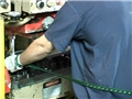 A machinist properly using a machine guard or safety device to avoid machine guarding hazards