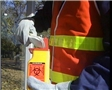 A worker preventing exposure to bloodborne pathogens by following safety training procedures