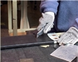 A worker following safe work practices while using a box cutter or utility knife to avoid injury