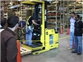 A safety trainer showing warehouse workers how to operate order selectors safely in the workplace