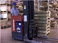 A warehouse worker safely operating a reach truck avoiding injury by following safe work practices